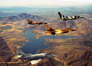 Two U.S. Navy/U.S. Marine Corps General Dynamics F-16N Viper and two Douglas A-4F Skyhawk of the United States Navy Fighter Weapons School (Top Gun) flying over Lower Otay Reservoir, Chula Vista, California (USA).